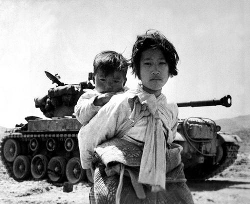 With her brother on her back a war weary Korean girl tiredly trudges by a stalled M-26 tank, at Haengju, Korea. June 9, 1951. Maj. R.V. Spencer, UAF. (Navy)